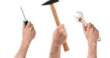 3 Hände halten Hammer, Schraubendreher und Schraubenschlüssel