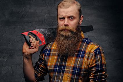 Mann mit Bart hält eine Säge
