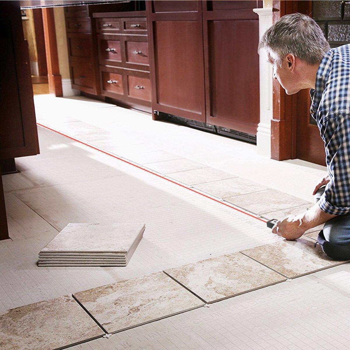 Mann misst Fußbodenlänge mit Laser-Entfernungsmesser